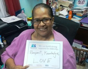 "A photo of C. Lewis, Executive Director , with her sign promoting, ""Respect, Knowledge Love,"" in support of elders."